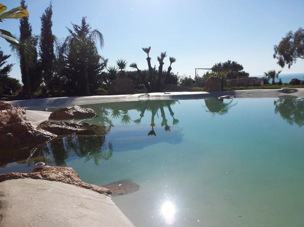 piscina effetto spiaggia con rocce artif