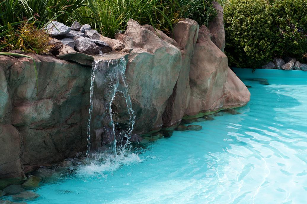 waterfall falling in a blue lagoon swimm