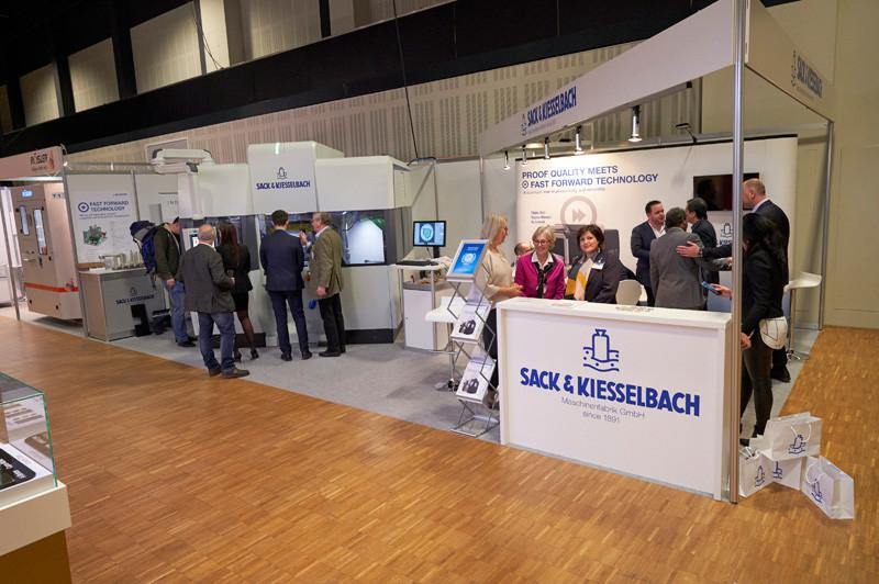 Der Messestand von Sack & Kiesselbach an der World Money Fair: An der Maschine erklärt Wolfgang Schmitz, während rechts im Stand Markus Schlein Kunden empfängt. Foto: Andreas Schoelzel / WMF.