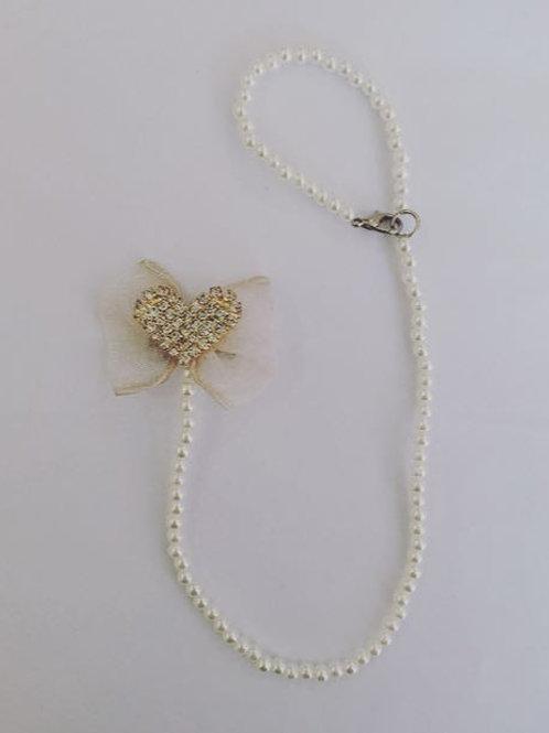 Prendedor de chupeta laço marfim coração strass