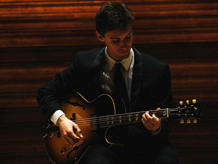Derek playing guitar in Wentz Concert Hall