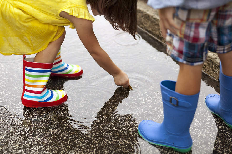 children in rainboots playing in a puddle