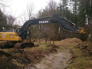 Exavating a ditch for farm drainage and erosion control