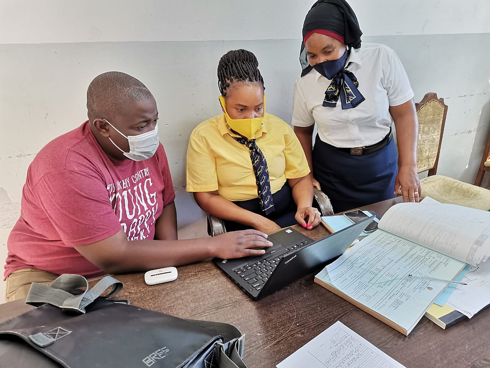 Three people wearing masks looking at a laptop