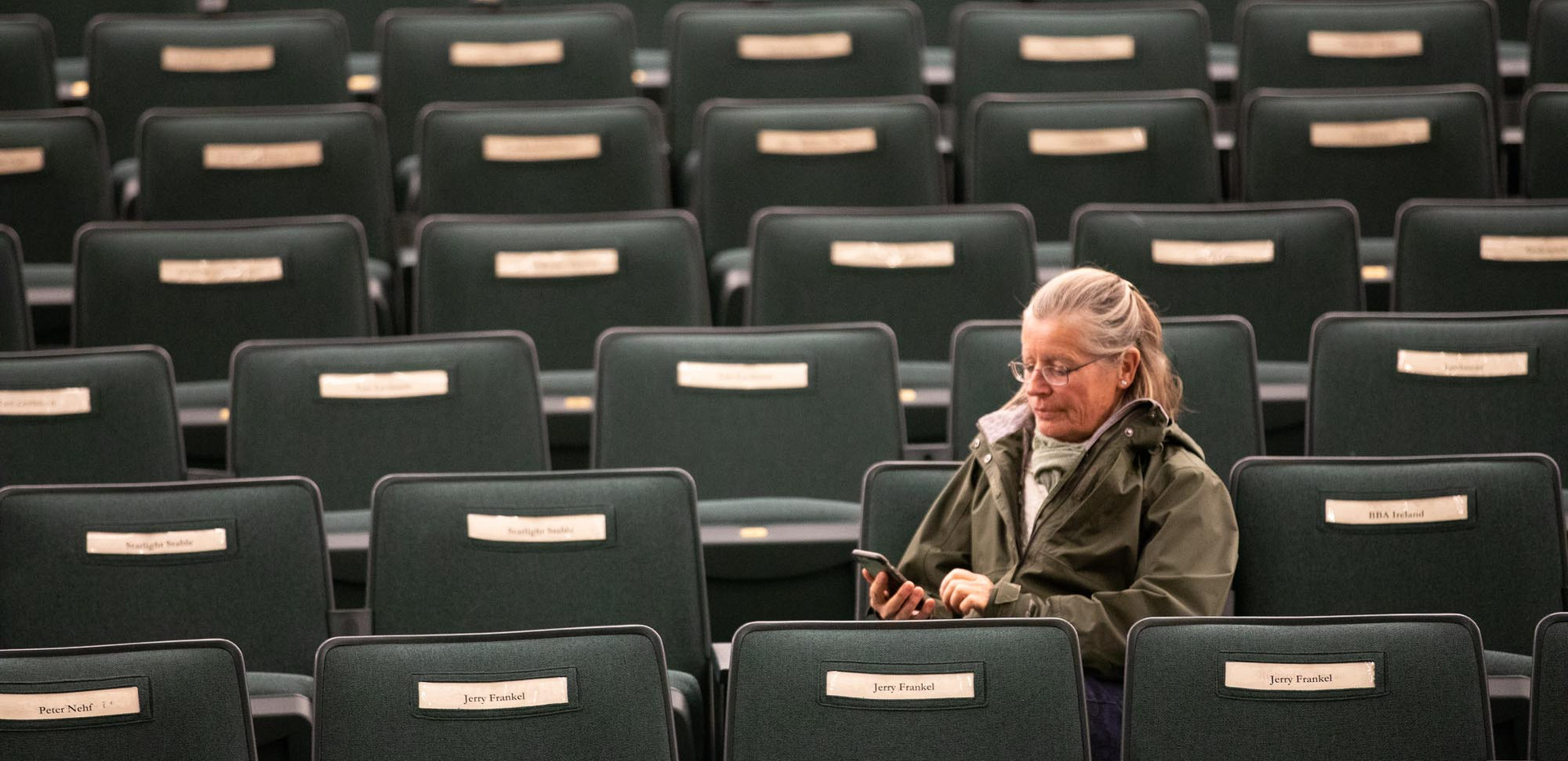 Lena sits in the auction house at Keeneland Race Track. Each buyer is assigned a seat  with a name plate. Lena does not have a reserved chair, but she soaks in the experience prior to watching a horse she bred race at Keeneland.