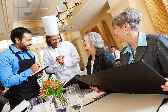 restaurant-chef-and-waiter-helping-custo