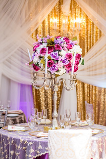 Flower center piece with purple linen and overlay and center piece with candles and flower decoration. China and glass ware with chiavary chairs.