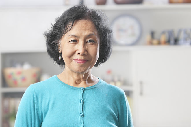 Senior Asian woman at home gazing to cam