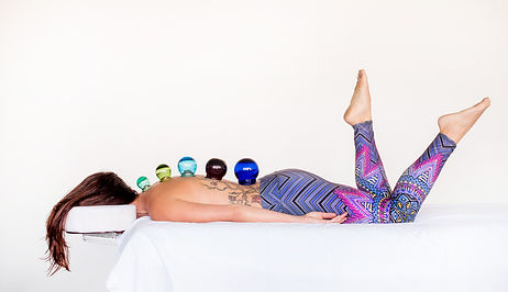 Woman laying prone on massage table with multicolored cups suctioned to her back, part of the Acupuncture Photo Project