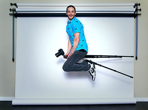 A cool man rides his tripod in front of his backdrop in his home studio. This is Lake View Chicago Portrait Photographer Mike Walburn.