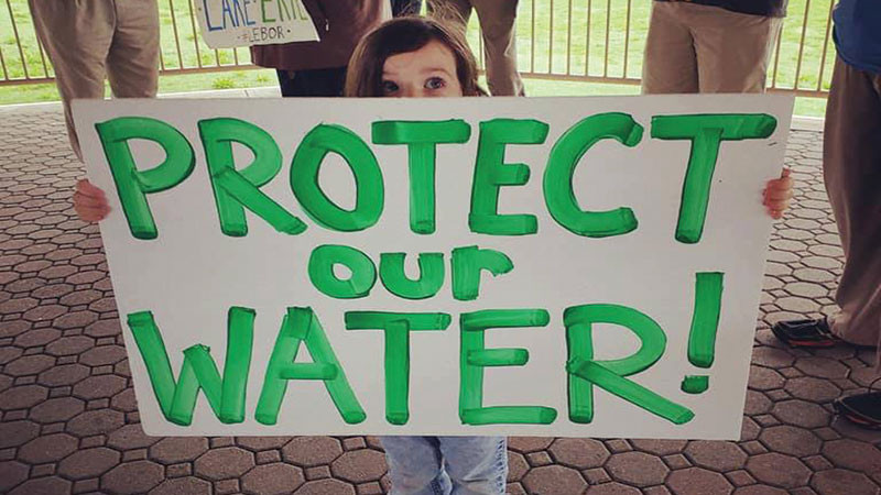 Amelia Jankowski, who was born during the water crisis four years ago, holding a sign at a press conference about ACLE endorsing the initiative.