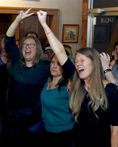 Toledoans for Safe Water activists, including organizer Markie Miller, left, reacts to the Lake Erie Bill of Rights passage during an election watch party at Michael's Bar & Grill in Toledo, Ohio, on Tuesday, Feb. 26, 2019.