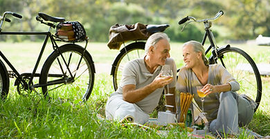 couple sittng on grass enjoying wine