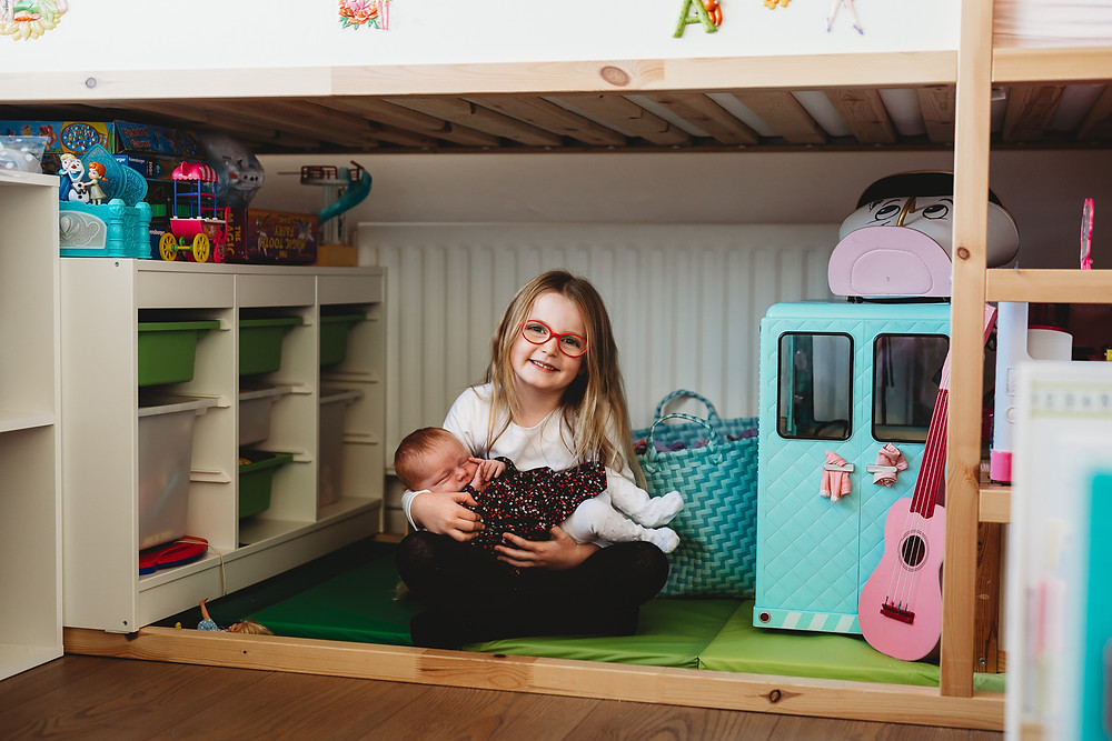 Girl and her newborn sister at home