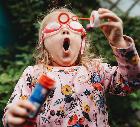 little girl blowing bubbles wearing goggles