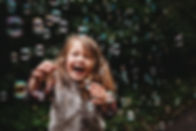 portrait of a girl laughing with bubbles