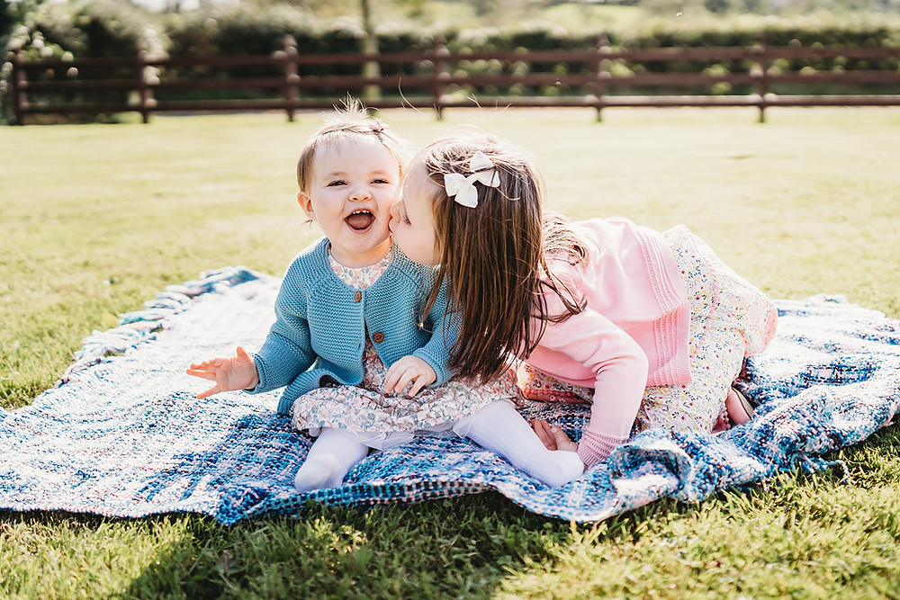 baby photoshoot, kissing baby sister on the cheek