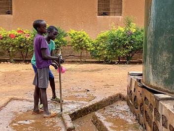 Dos niños invidentes en la fuente de agua
