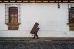 Man carries wardrobe along a road