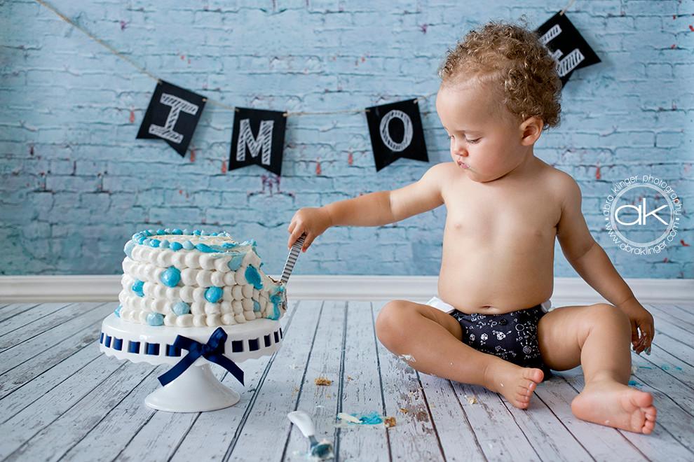 1 year old boy poking at cake