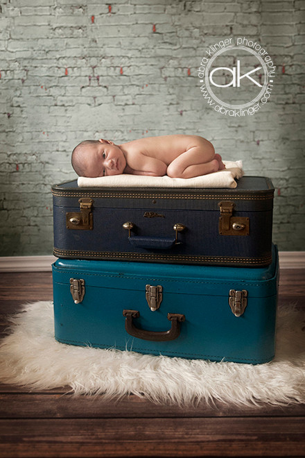 Boy on tummy on top of stack of suitcases