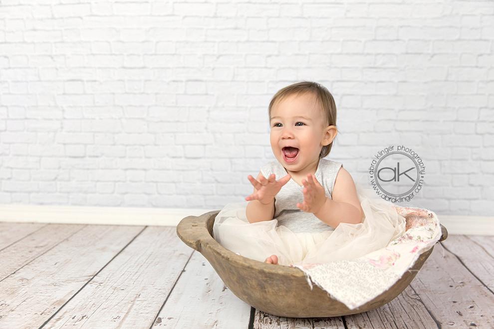 Happy girl in wooden bowl