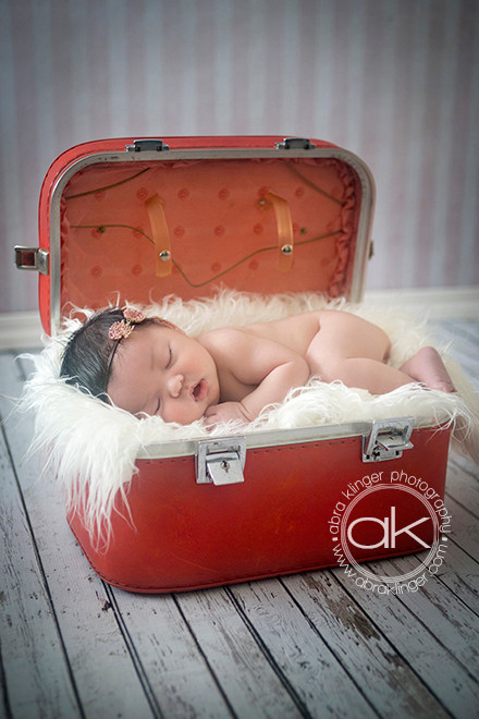 Newborn in red suitcase