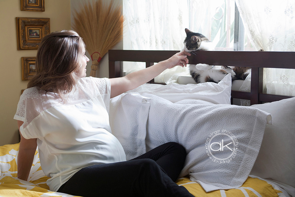 Expecting mom reaches out to cat
