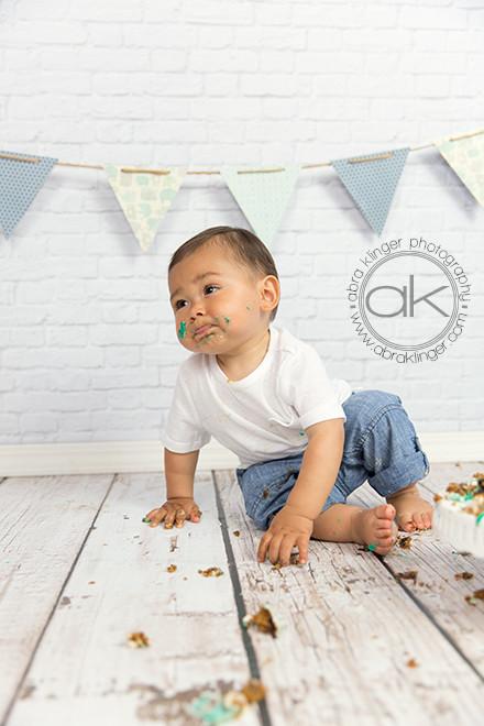 Boy making funny face during his cake smash