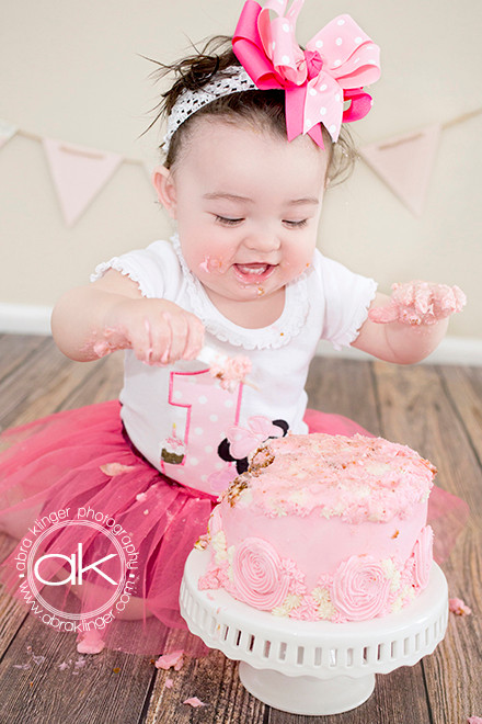 Little girl digging into cake