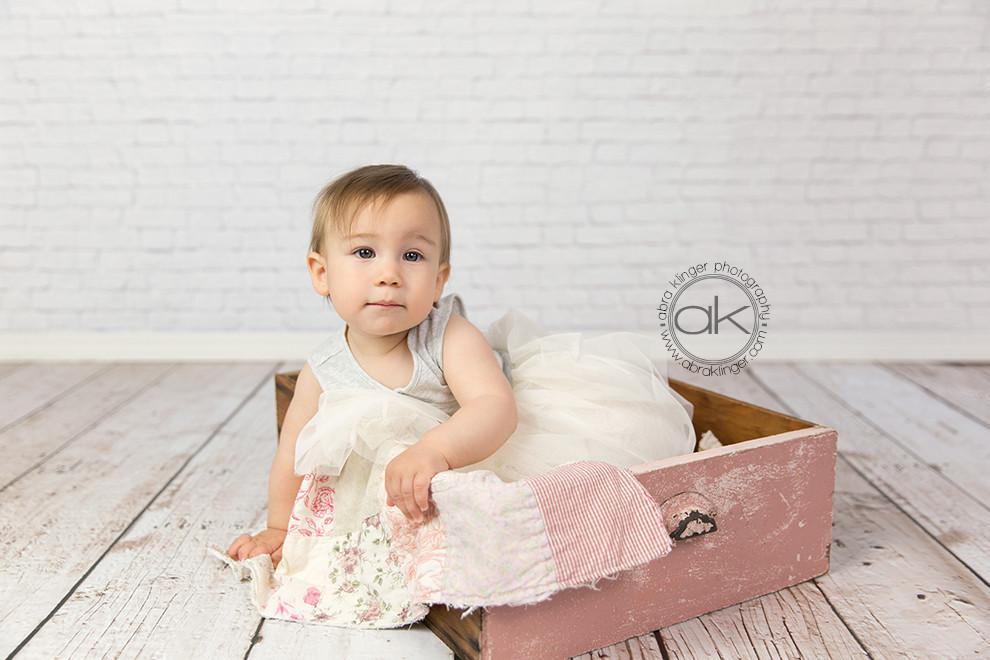 Girl sitting in pink drawer