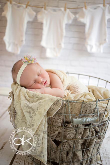 Newborn girl in basket with onesies