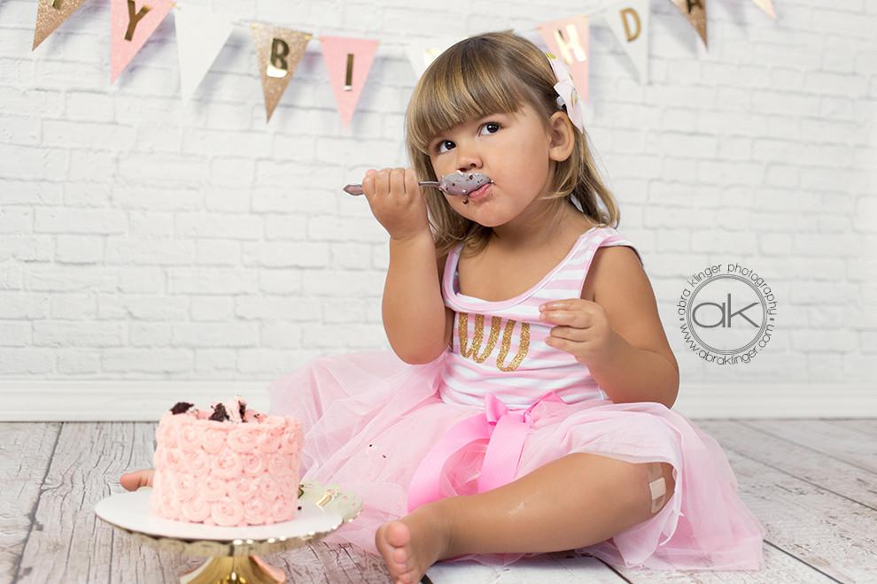 Young girl eats birthday cake