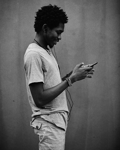 Black man standing against a grey wall holding his earphones and phone_edited_edited.jpg