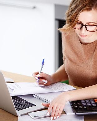 Woman sitting at laptop computer, making