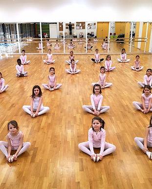Cours de danse éveil et initiation de l'association Les Corps Dansants à Nantes, de jeunes ballerines de 4 à 7 ans en tenue de danseuse classique se tiennent assise sur le parquet de la salle de danse