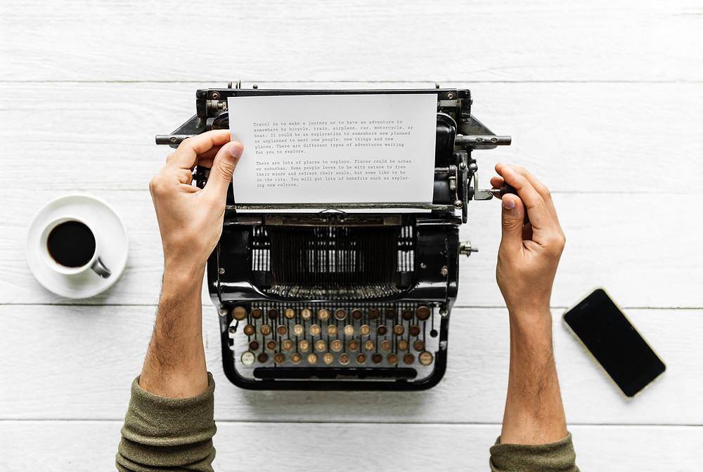 Man typing a scientific manuscript on a typewriter