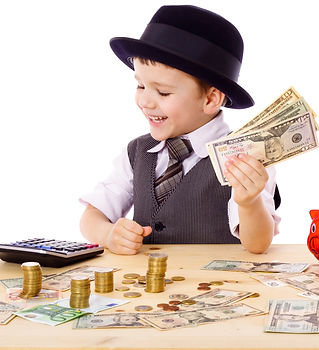 Little boy in black hat and tie at the table counts money, isolated on white.jpg