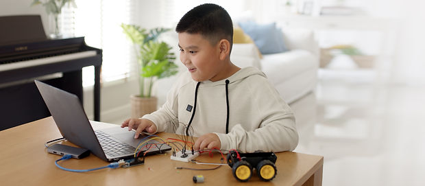 Young asia student remotely learn online at home in coding robot car and electronic board