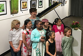 Candace and 7 of her students gather for a picture in front of the piano after the June 2019 recital.