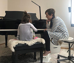 Kara is sitting on the piano bench in a very comfortable position as she begins her first lesson with Candace.