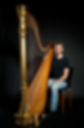 Oliver Wass holding a harp in a photoshoot