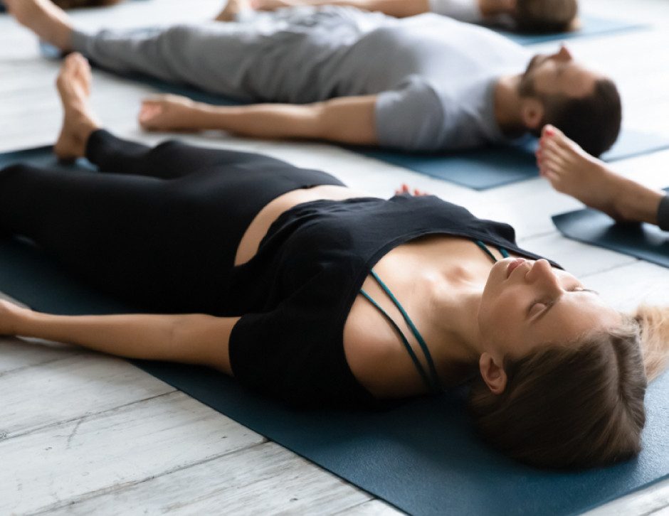 young woman meditating in Savasana pose, yoga in group class, training, working out, modern yoga