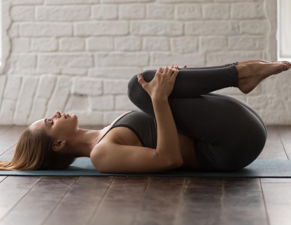 Young woman, yoga, apanasana, working out, home, yoga studio