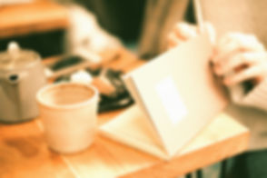 person opening book near coffee cip_edited_edited.jpg