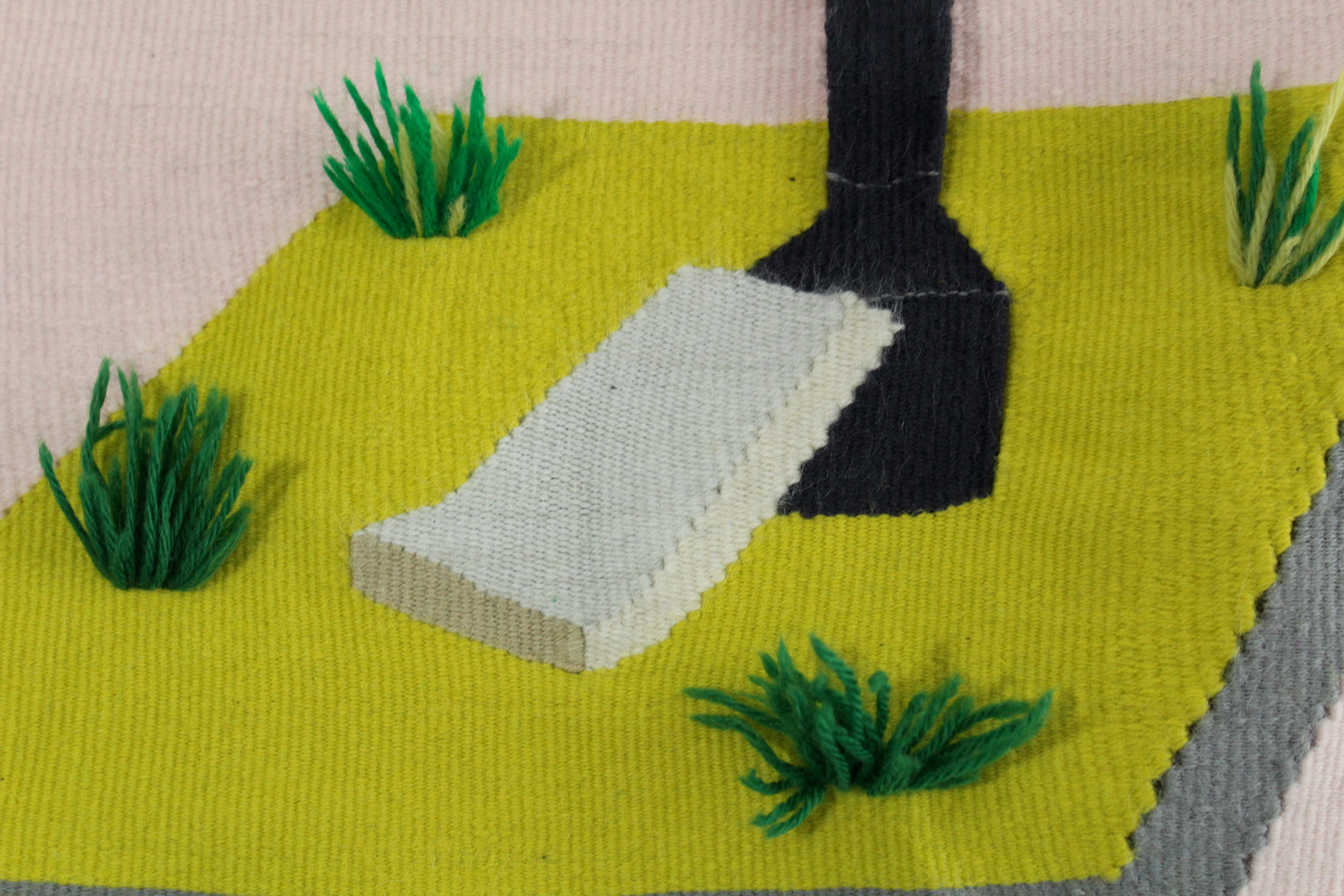 A grassy island with daffodils and a couch cushion, detail