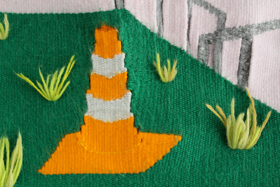 A grassy island with daffodils and a traffic cone, detail