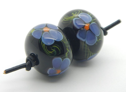 Floral bead pair handmade lampwork glass purple, green and black angle