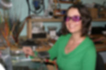 lampwork glass bead & jewelry artist Larissa Spafford at her torch in her studio in Bend, Oregon