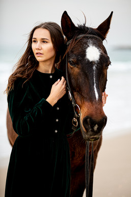 young  woman with brown  horse on the beach